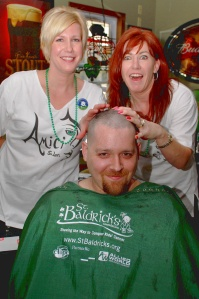 Carrie Gobeille and Susan Shlosser show off their handy work performed on Jason Jordan during the annual St. Baldrick's Foundation Event that raised money for children's cancer research held at the Southwick Inn last Sunday.